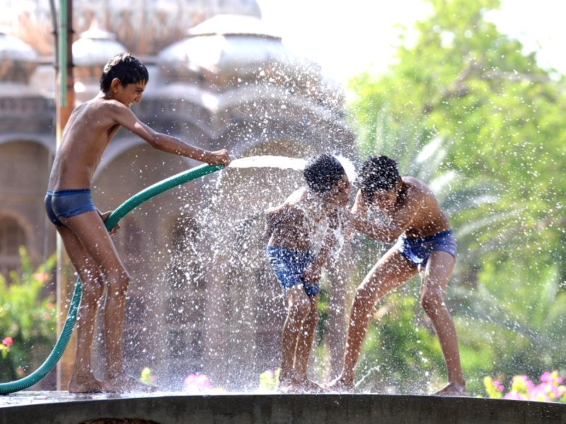 Children play with water on a hot day in Jodhpur on May 19, 2017.