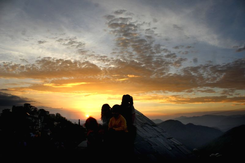 Children pose for a picture with a view of spectacular sky behind them in Shimla, on June 23, 2016.