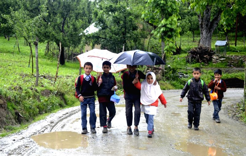 Children return back from school on a rainy day in Baramulla of Jammu and Kashmir on May 17, 2017.