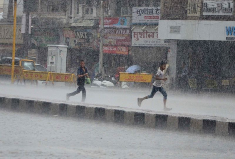 Children run to take shelter as rains lash Bhopal on June 9, 2018.