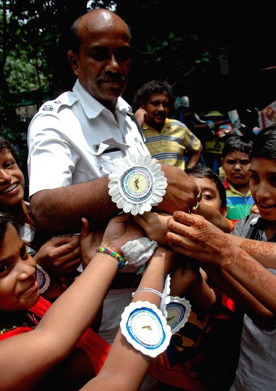 Children tie a `rakhi` to a policeman on `Raksha Bandhan` in Kolkata on Aug 10, 2014.