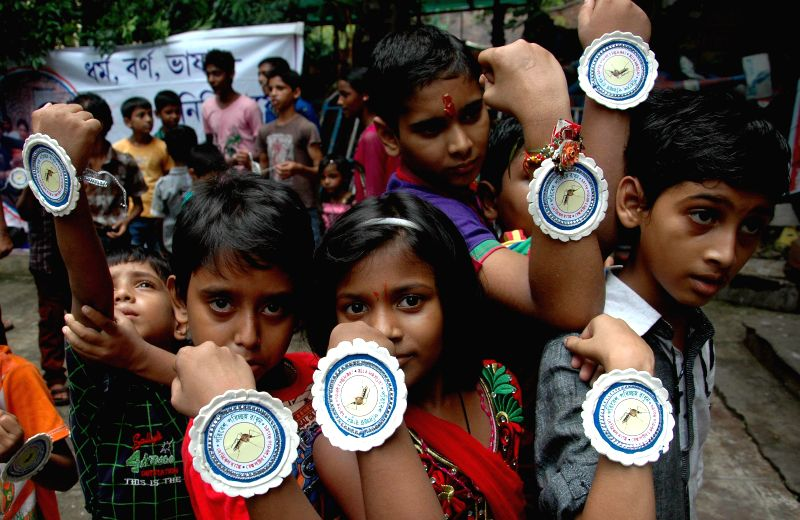 Children tie a `rakhi` with a picture of mosquito to spread awareness regarding vector-borne diseases on `Raksha Bandhan` in Kolkata on Aug 10, 2014.