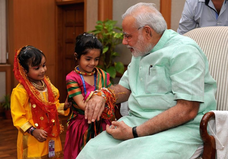 Children tie 'rakhi' to Prime Minister Narendra Modi on the occasion of 'Raksha Bandhan', in New Delhi on August 10, 2014. - Narendra Modi