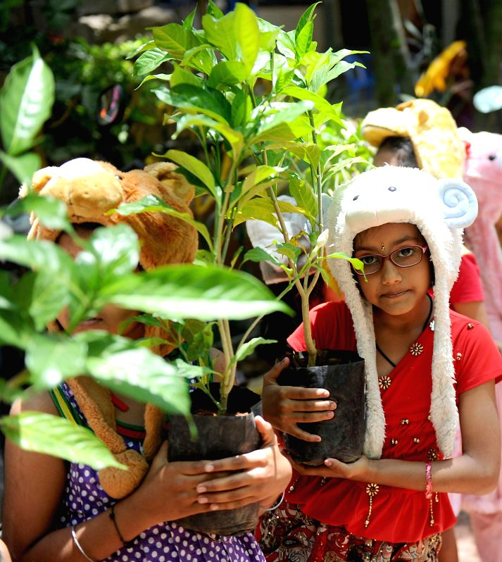 "Children wearing animal caps hold plants during the ""World Earth Day"" organised by Bharatiya Samaja Seva Trust at Makkala Koota in Bangalore on April 22, 2014."