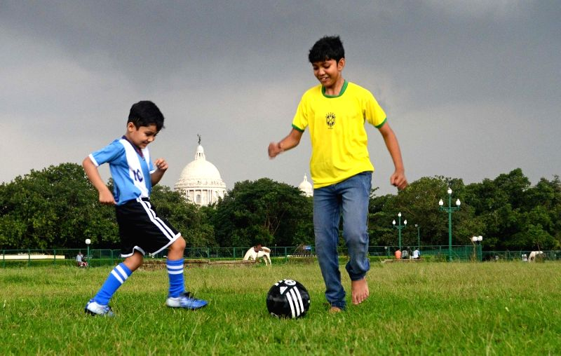Children wearing jersey of Brazil and Argentina busy playing football on an overcast day in Kolkata, on Jun 10, 2018.