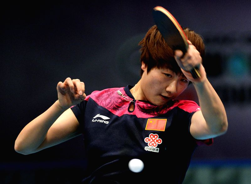 China's Ding Ning returns a shot against Portugal's Fu Yu during their women's singles match of the 2015 ITTF World Tour Grand Finals in Odivelas, outskirts of ...
