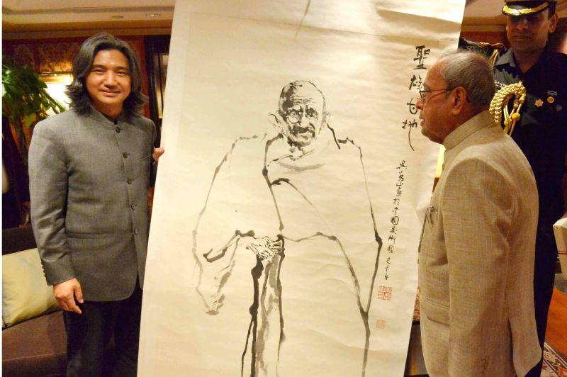 Chinese artist Han Meilin gifts a sketch of Mahatma Gandhi to President Pranab Mukherjee in Beijing, China on May 25, 2016. - Han Meilin and Pranab Mukherjee