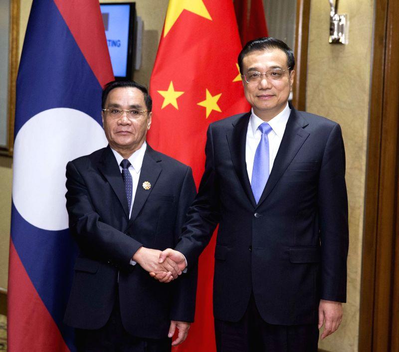 Chinese Premier Li Keqiang (R) meets with his Lao counterpart Thongsing Thammavong in Kuala Lumpur, Malaysia, Nov. 21, 2015. (Xinhua/Huang Jingwen)