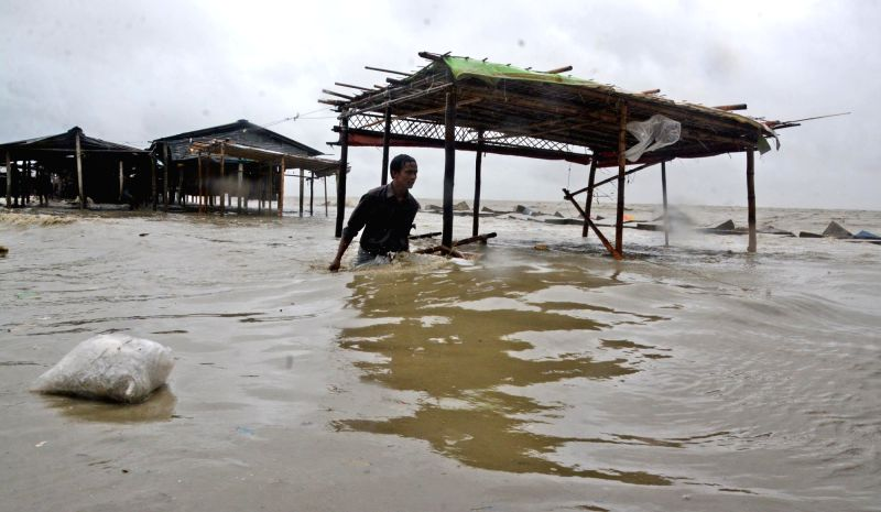 CHITTAGONG, May 22, 2016 - A man wades in water in southernmost coastal district of Bangladesh, on May 21, 2016. Cyclone Roanu slammed into the Bangladesh coastlines after making landfall in a ...