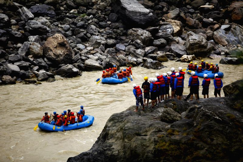 Nepalese people and tourists enjoy white water rafting in Trishuli river, Chitwan, Nepal, April 13, 2015.