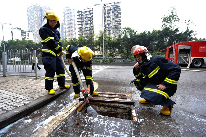 Fire fighters flush water at the site of a gasoline leak near a light railway station in southwest China's Chongqing, April 11, 2014. The leak occurred around 11