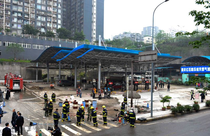 Fire fighters deal with the accident at the site of a gasoline leak near a light railway station in southwest China's Chongqing, April 11, 2014. The leak ...