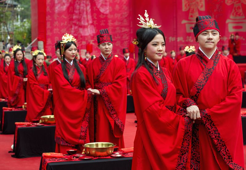 Brides and grooms hold hands during a Chinese wedding in southwest China's Chongqing, May 2, 2014. Wearing Hanfu, the traditional Chinese costume, 52 couples got ...
