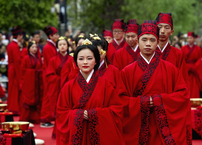 Brides and grooms head for a Chinese wedding in southwest China's Chongqing, May 2, 2014. Wearing Hanfu, the traditional Chinese costume, 52 couples got married ...