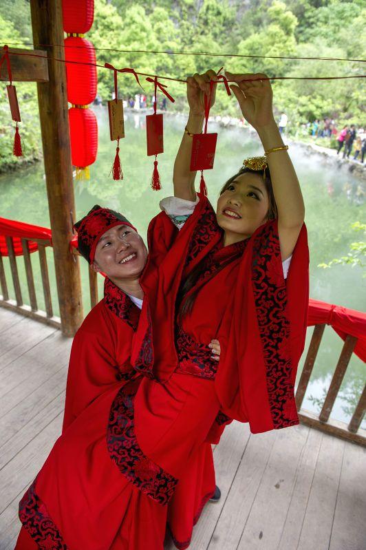 Zheng Geng (L) and his bride Zou Daqiao hang a wooden plaquette symbolizing love during a Chinese wedding in southwest China's Chongqing, May 2, 2014. Wearing ...