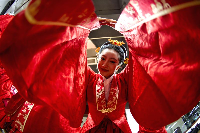A bride wearing Han clothing attends a group wedding ceremony at the Taohuayuan scenic area in Youyang, southwest China's Chongqing, May 2, 2015. A total of 99 ...