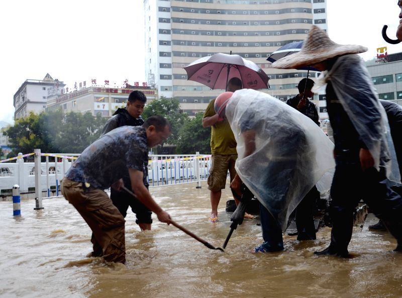 Municipal workers dredge drainage in Wuxi County, southwest China's Chongqing Municipality, Sept. 1, 2014. Affected by a rain-triggered flood starting from Aug. ..