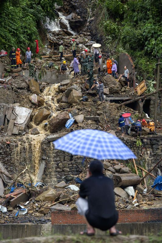 A villager watches the rescuers working at the landslide site at Tuantan Village in Yunyang County, southwest China's Chongqing Municipality, Sept. 2, 2014. Eight