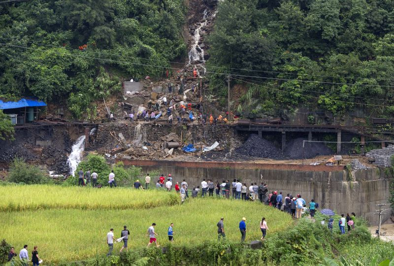 Local villagers gather around the landslide site at Tuantan Village in Yunyang County, southwest China's Chongqing Municipality, Sept. 2, 2014. Eight people died .