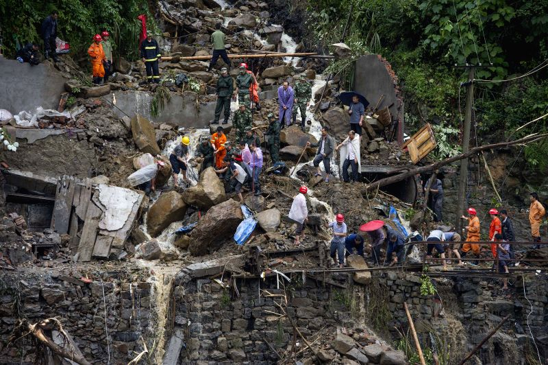 Rescuers work at the landslide site in Tuantan Village of Yunyang County, southwest China's Chongqing Municipality, Sept. 2, 2014. Eight people died and 24 others