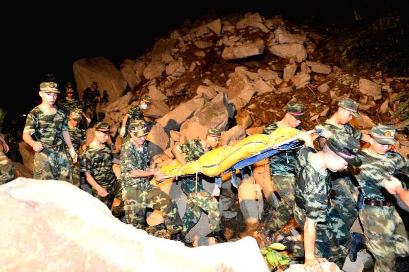 Rescuers transfer the body of a victim after a rainstorm-triggered landslide hit Yongfa Coal Mine in Jiangkou Township of Yunyang County, southwest China's ...