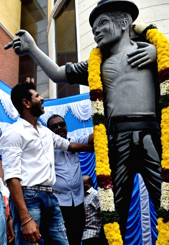 Choreographer and filmmaker Prabhu Deva with the newly installed 12-ft tall statue of late US pop star Michael Jackson at a Chennai university on April 7, 2016.