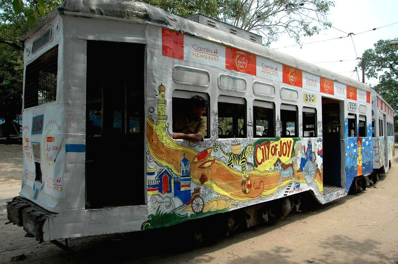 Citizens paint a tram car as part of an art exhibition in Kolkata on April 19, 2014.