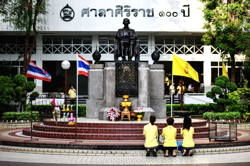 Citizens pray in front of a sculpture of King Bhumibol Adulyadej as they observe the King's 88th birthday inside the Siriraj Hospital, where the King currently ...