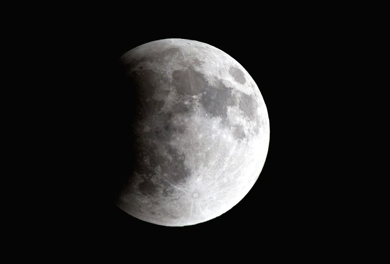 The Moon is seen at the beginning of an eclipse, in the sky above Mexico City, capital of Mexico, early April 15, 2014. The eclipse made the Moon look ...