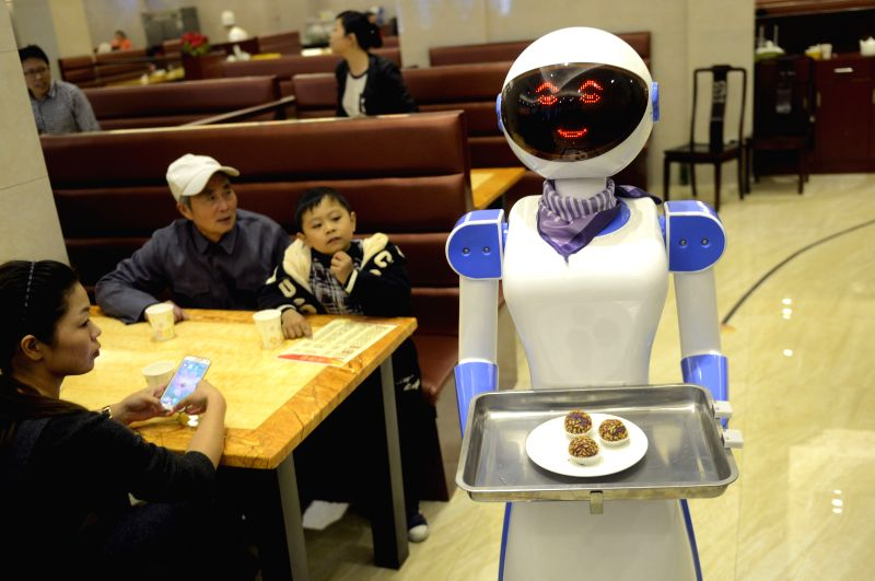 Cixi (China): A server robot delivers food at a restaurant in Cixi, east China's Zhejiang Province, Nov. 27, 2014. A newly opened restaurant in Cixi has introduced two server robots which can help ...