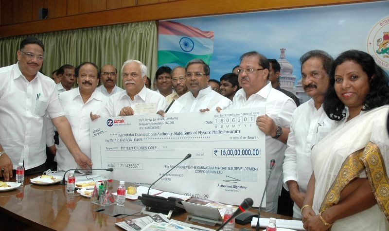 CM Siddaramaiah handing over cheque of Rs.15 crores to Karnataka Examination authority towards pre-educational loan to students pursuing professional courses belonging to religious minorities at home