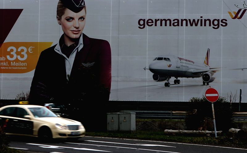 A taxi drives past a poster of Germanwings near its headquarters in Cologne, Germany, on March 24, 2015. There are no Chinese passengers onboard the crashed ...
