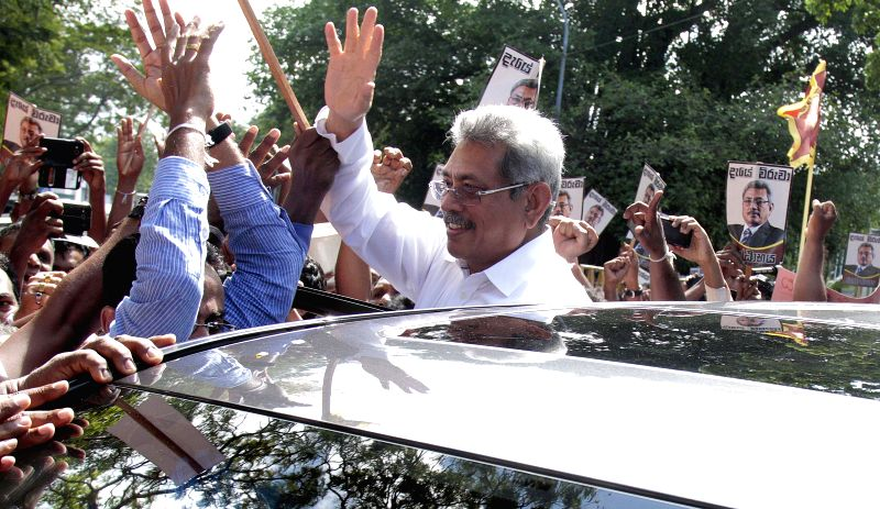 Sri Lankan former Defense Secretary Gotabaya Rajapakse (C) greets his supporters as he arrived at the anti-graft commission office in Colombo, capital of Sri ...