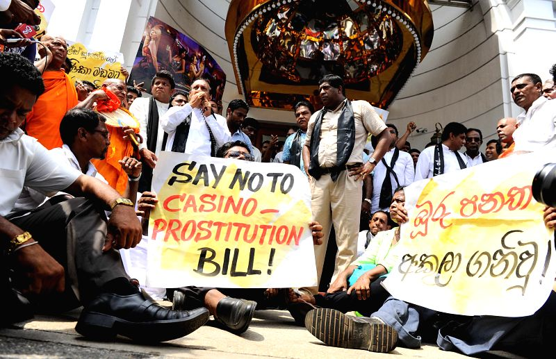 Supporters of Sri Lankan main opposition hold banners as they protest outside a casino in Colombo, Sri Lanka, on April 24, 2014. The opposition objected to ...