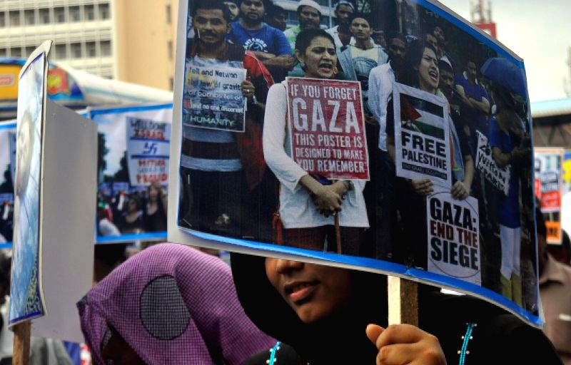 A protestor holds a placard during a protest against Israel's military campaign in Gaza, in front of the Fort Railway Station in Colombo, Sri Lanka, on Aug. 19, ...