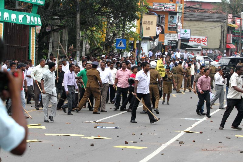 Protesters holding clubs and stones gather outside the opposition United National Party (UNP)'s headquarter in Colombo, capital of Sri Lanka, Dec. 24, 2014. As a ...
