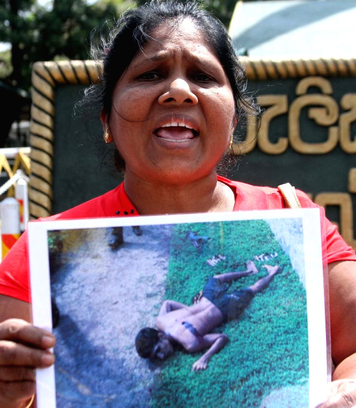 A woman holding a picture participates in a protest in Sri Lanka's capital Colombo, on Feb. 17, 2015. Hundreds of people participated in a massive protest staged ...
