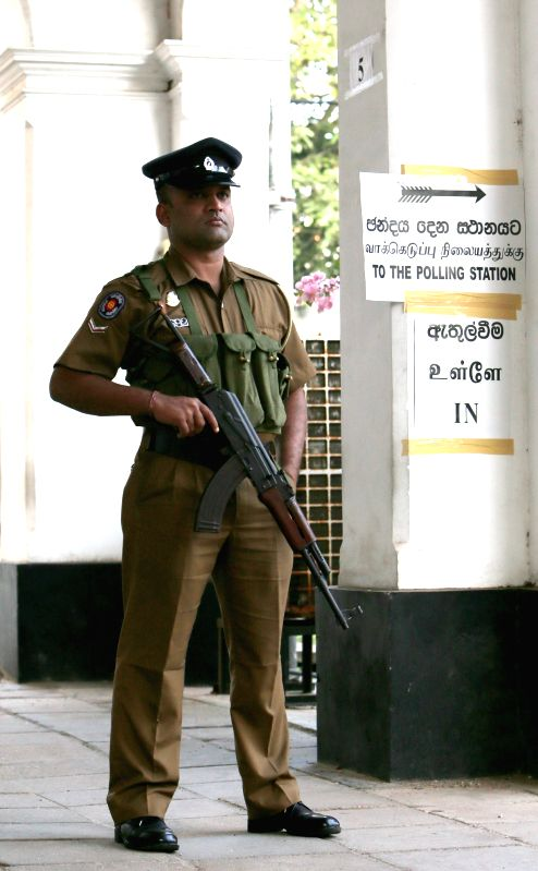 A policeman stands guard outside a polling station in Colombo Jan. 8, 2015. Sri Lanka held presidential election on Thursday.
