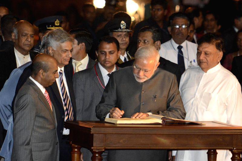 Indian Prime Minister Narendra Modi signs his name on the national book in Sri Lanka, March 13, 2015. Indian Prime Minister Narendra Modi arrived in Sri Lanka on ... - Narendra Modi