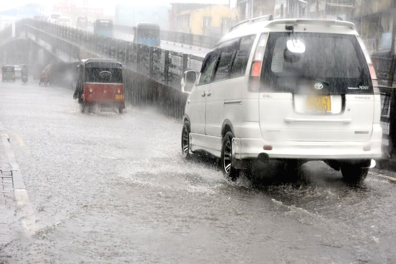 COLOMBO, May 15, 2016 - Vehicles wade through a flooded street in a district near Colombo, Sri Lanka, May 14, 2016. Sri Lanka's Disaster Management Center (DMC) issued landslide warnings to seven ...