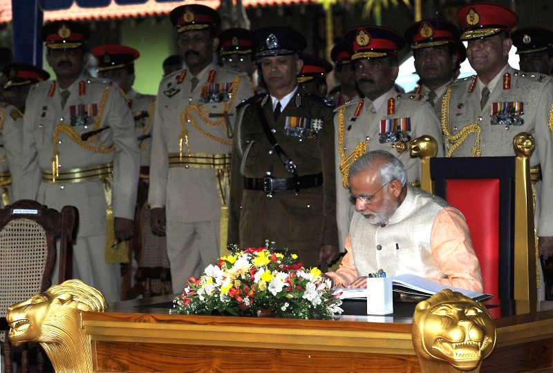 Prime Minister Narendra Modi signs the visitor`s book after paying tributes to the martyrs of the Indian Peace Keeping Force soldiers, in Colombo, Sri Lanka on March 13, 2015. - Narendra Modi