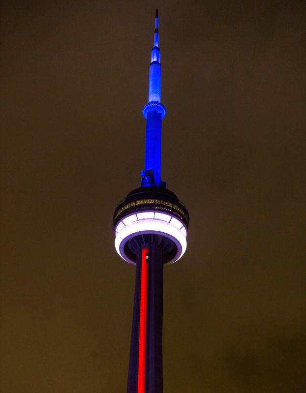 Colors that resemble the French national flag are seen on the Canadian National Tower in Toronto, Nov. 13, 2015. Over 100 people were killed in a mass ...