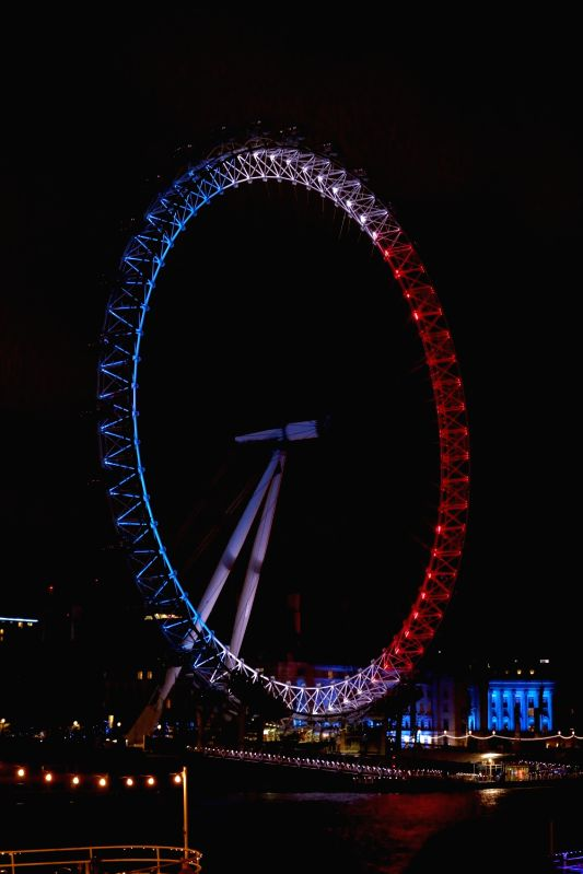 Colors that resemble the French national flag are seen on the London Eye in London, Britain, on Nov. 14, 2015. The provisional death toll of Paris attacks is 129 and ...