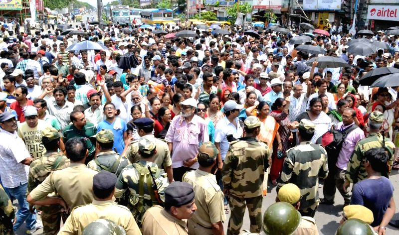 Communist Party of India-Marxist (CPI-M) workers block busy arterial B T Road to protest against Belghoria violence a day ahead of 9th phase of 2014 Lok Sabha Elections in North 24 Parganas district .