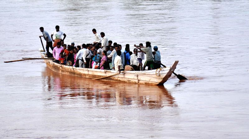 Commuters are forced to take a boat to cross swollen Koel River as the sole bamboo bridge over the river has been washed away, in Rourkela of Odisha's Sundergarh district on July 23, 2014.