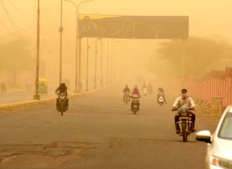 Commuters cover their faces to protect themselves from dust as dust storm hits Bikaner on June 14, 2018.