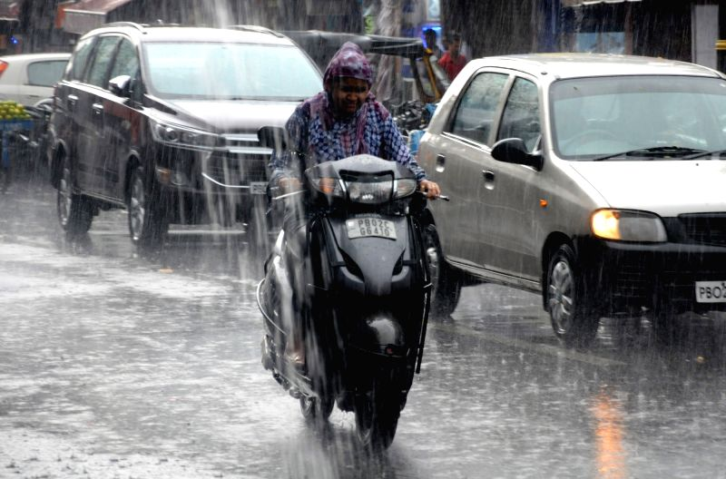 Commuters during rains, in Amritsar on July 25, 2018.