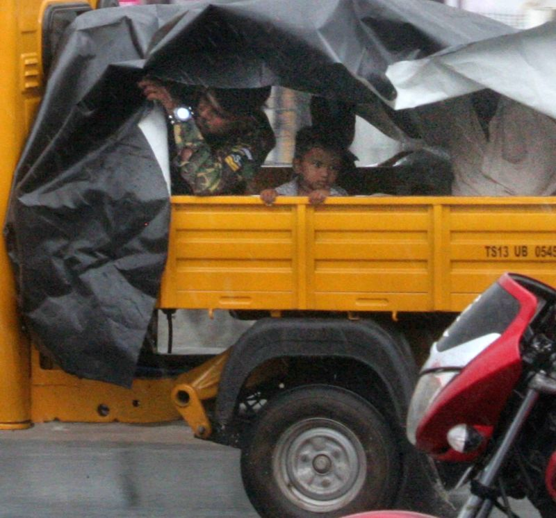 Commuters during rains, in Hyderabad on June 12, 2018.