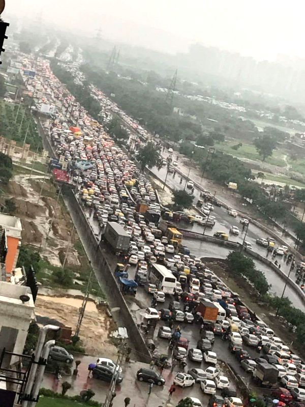 Commuters stranded at NH 24 due to heavy rains, in Noida, on July 27, 2018.