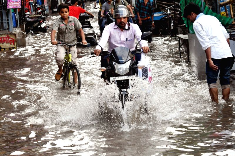 Commuters struggles through a water-logged street after heavy rains, in Patna on July 26, 2018.